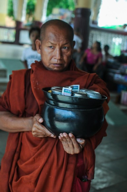 Monk with lam bowl full of offerings