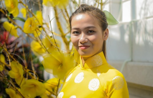 Beautiful girl in ao day with Tết flowers